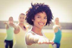 smiling-sporty-woman-doing-yoga-yoga-class-portrait-women-parkland-58190301